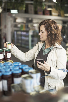 Woman holding smart phone while reading label on bottle in supermarket