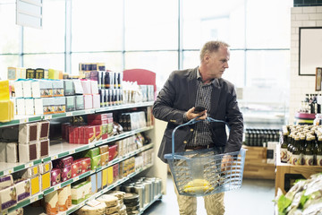 Mature man buying groceries in supermarket