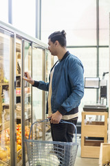 Man opening refrigerator while shopping groceries in supermarket