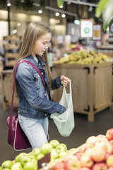 Girl buying apples in supermarket