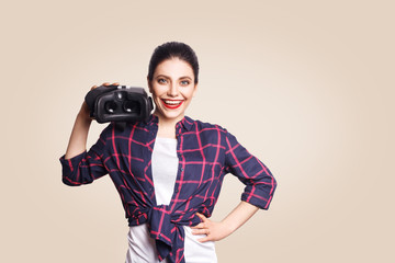 Young beautiful woman in casual style with virtual reality headset on beige background. studio shot. .