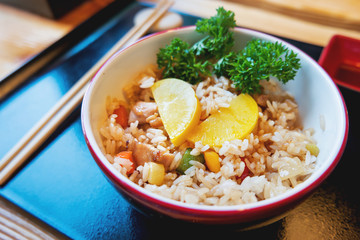 Asian cuisine - Tori tyahan. Fried rice with chicken meat, vegetables and radishes in bowl.