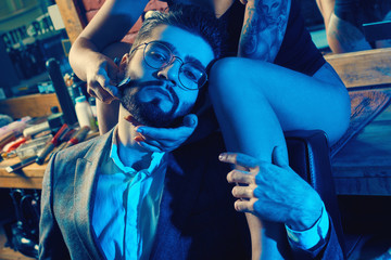 Brutal man in elegant suit and sexy girl with tattoo