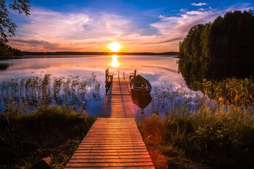Sunset over the fishing pier at the lake in Finland