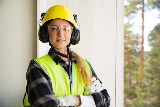 Portrait of a Young Female construction worker in hard hat drilling concrete wall with a drill and smiling at the camera. Building and renovation. feminism concept.