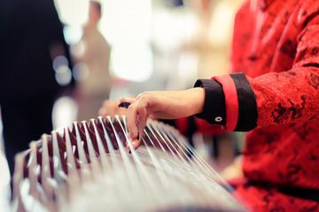 hand of man playing Guzheng.The guzheng or gu zheng, also simply called zheng, is a Chinese instrument