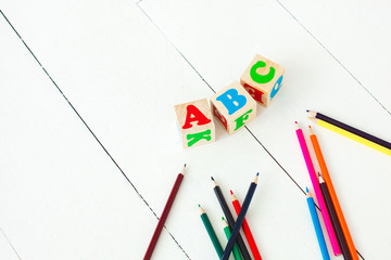 wooden english abc cubes and colorful pencils on the white neutral background.