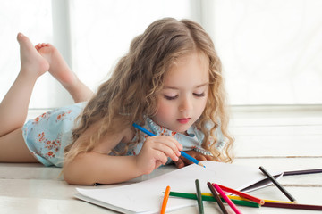 Cute little girl drawing with colorful pencils on paper. Pretty little child drawing indoors.Adorable artist