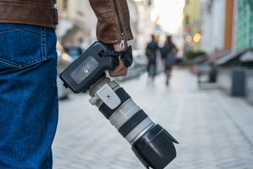 Photographer with camera and telephoto lens outdoors