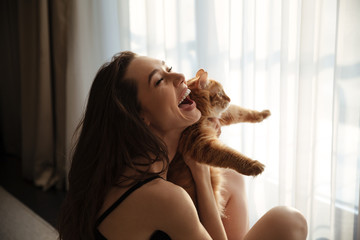 Cheerful woman holding red cat and laughing at home