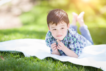 Mixed Race Chinese and Caucasian Young Boy Relaxing Outside On The Grass