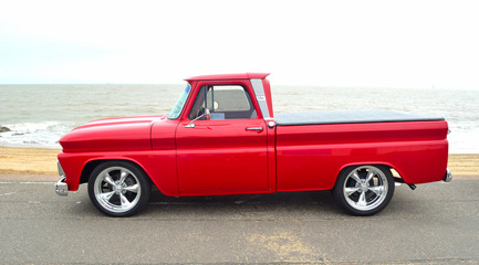 Classic Red  American pickup truck on seafront promenade.
