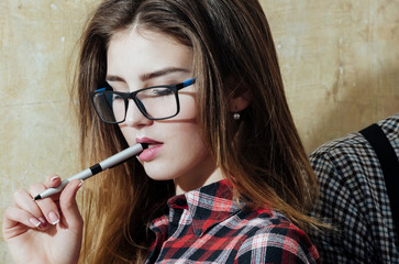 Pretty girl student in nerd glasses holding pen in mouth