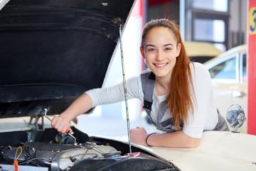 Female mechanic working on a car engine