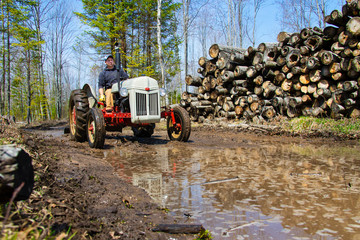 Man driving a vintage tractor on a muddy road.