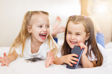 people, children, technology, friends and friendship concept - happy little girls with smartphones lying on floor at home education, school are using a smartphone and smiling while sitting on sofa