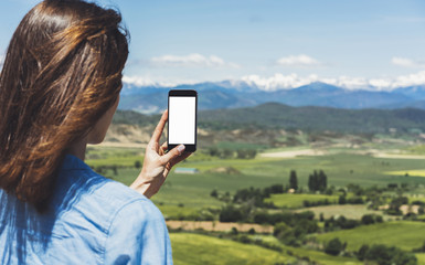 Hipster photograph on smart phone gadget mobile, mock up of blank screen. Girl traveler hold in hand mobile on background mountain landscape horizon. Tourist on adventure trip, lifestyle concept