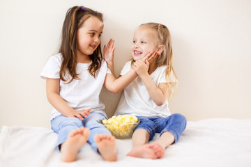 Portrait of beautiful young sisters eating popcorn at home. Two children eat popcorn against the white background