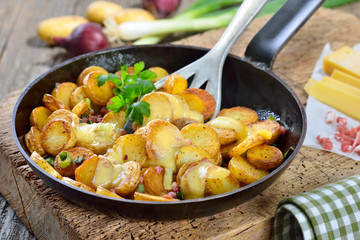 Rustikaler Snack: Ungeschälte Mini-Bratkartoffeln mit Speck und Frühlingszwiebeln überbacken mit reifem Bergkäse - Fried unpeeled baby potatoes with melted mountain cheese and bacon cubes