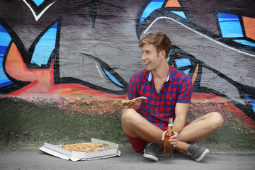 Young handsome man with pizza and beer sitting on asphalt on painted wall background
