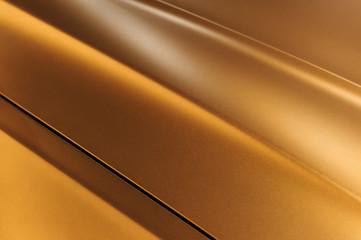 Surface of bronze sport sedan car metal hood, part of vehicle bodywork, steel gradient line pattern, selective focus