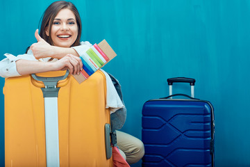 Smiling young woman with two suitcase shows thumb up.