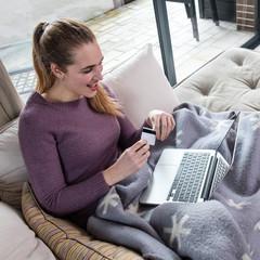 joyful young beautiful woman shopping online for winter season