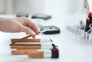 Professional makeup artist taking brush at beauty salon