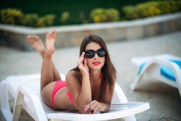 A beautiful girl in a pink bathing suit sunbathing by the pool. Sunny weather. Summer.