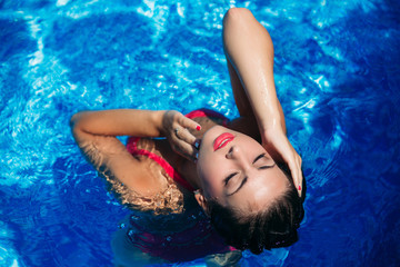 A young girl is swimming in the pool near the beach, sunny weather. Summer