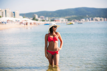 Beautiful girl in a pink bathing suit, in the sea. Sunny weather. Summe