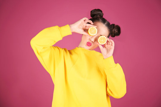 Beautiful young woman with lemon on color background