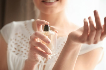 Beautiful young woman with bottle of perfume at home, closeup Wall mural