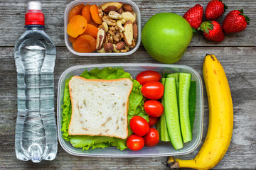 Healthy lunch boxes with sandwich and fresh vegetables, bottle of water, nuts and fruits