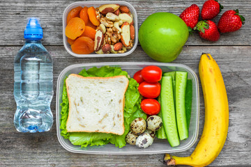 school lunch boxes with sandwich, eggs and fresh vegetables, bottle of water, nuts and fruits