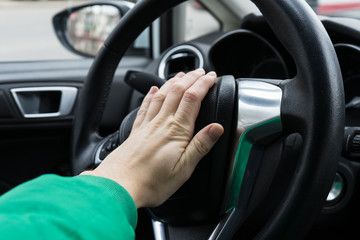 Nervous man driver pushing car horn , close up view of hand on the steering wheel
