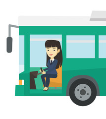 Asian bus driver sitting at steering wheel.