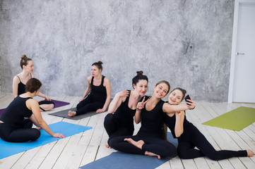 Three young women making selfie after workout at yoga class