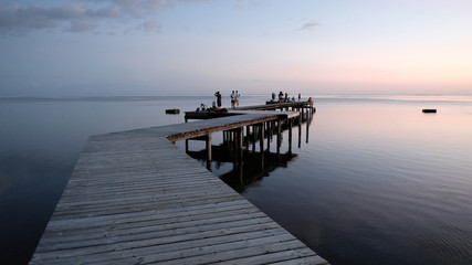 Wooden jetty and silhouette of people at sunset, Tahiti, South Pacific