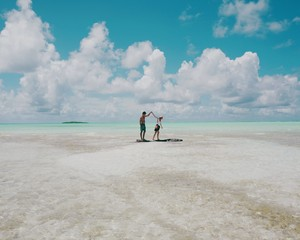 Couple holding hands and playing in shallow sea water