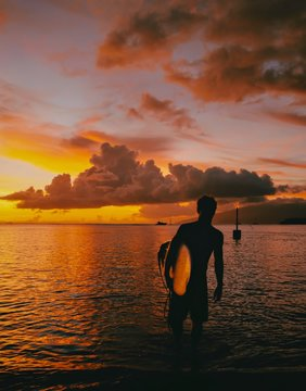 Silhouette of man standing in sea with surfboard during sunset
