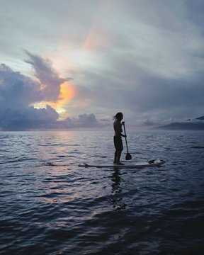 Silhouette of man standing on surfboard at sea, sunset background