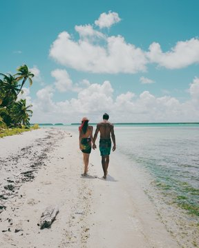 Rear view of couple holding hands while walking on beach