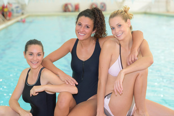 Portrait of three ladies by swimming pool