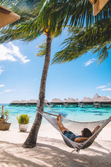 Man reclining in hammock by sea, distant beach huts, Mo'orea, South Pacific