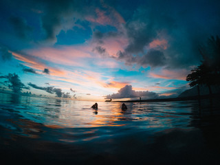 Feet poking out of sea at sunset, Tahiti, South Pacific