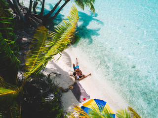 Aerial view of couple relaxing on island beach with palm trees, Tahiti, South Pacific