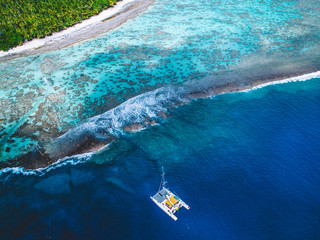 Aerial view of island coastline, boat on water near island, Tahiti, South Pacific