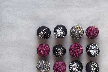 Various fitness bites, raw chocolate truffles, with rose petals, on gray concrete background. Food photography, diet concept