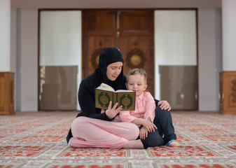 Mother reading Koran to her son in mosque